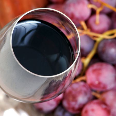 Glass of red wine with grapes.